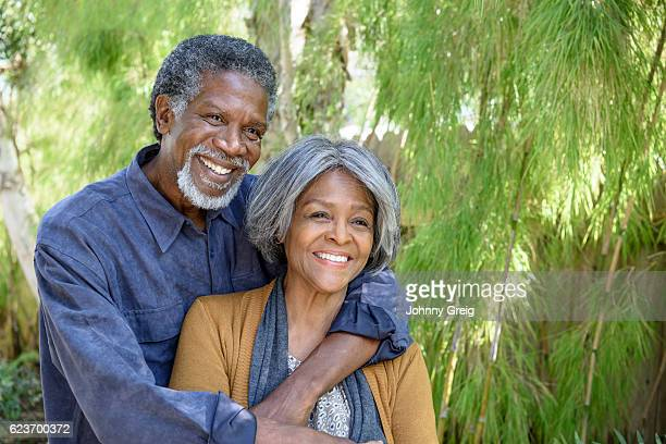 Cheerful senior African American couple in garden, smiling