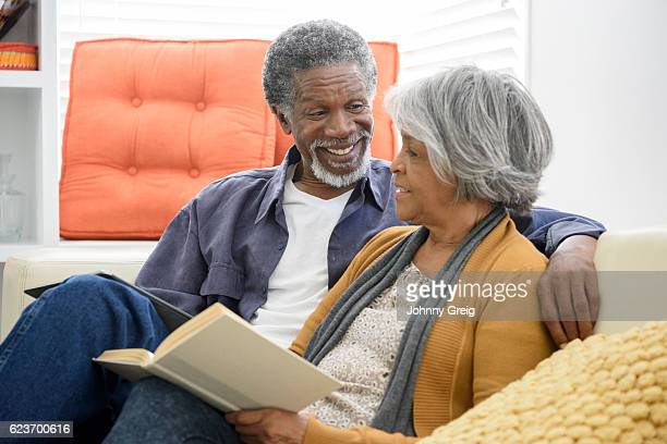 Cheerful senior African American couple laughing on sofa