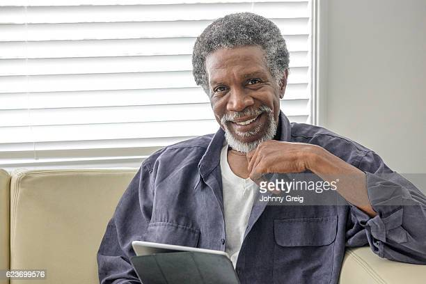 Cheerful senior African American man using tablet at home