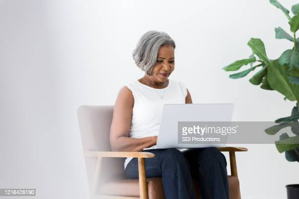 cheerful senior business woman works from home - avoidance stock pictures, royalty-free photos & images