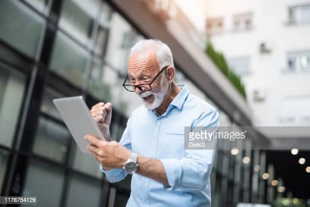 homme d'affaires aîné gai voyant de grands résultats sur une tablette numérique. - bonne nouvelle photos et images de collection
