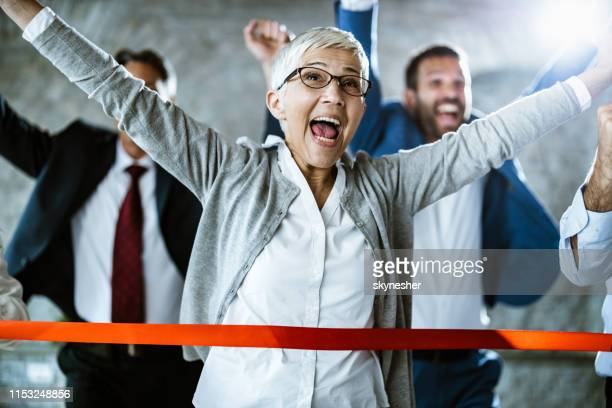 cheerful senior businesswoman celebrating her success while crossing the finish line in the office. - finish line stock pictures, royalty-free photos & images