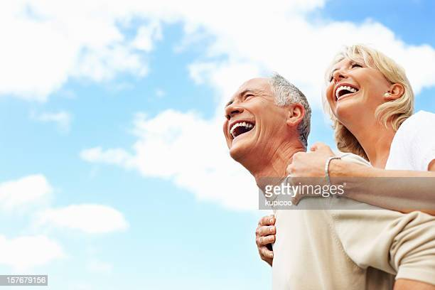 Cheerful senior couple against sky