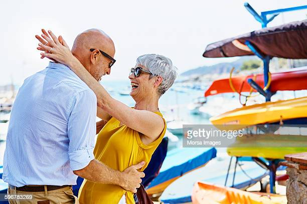 Cheerful senior couple dancing by harbor