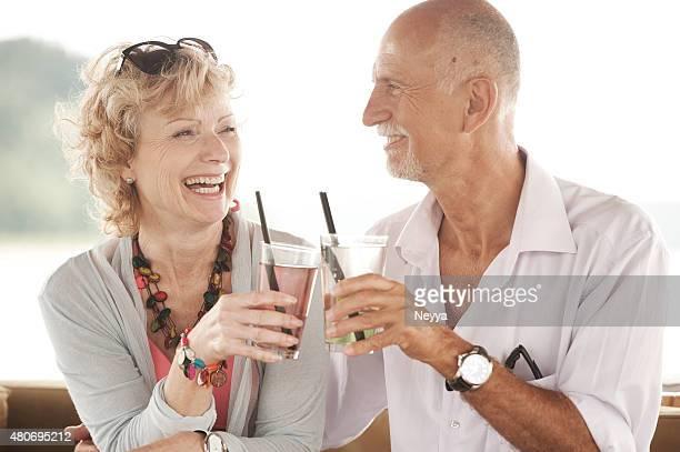 fröhlich altes paar genießen sie den tag am strand - heterosexuelles paar stock-fotos und bilder