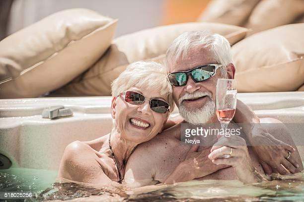 陽気な年配のカップル楽しみながらサマー Vaccation のジェットバス