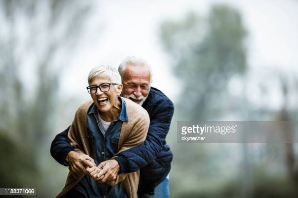 cheerful senior couple having fun in the park. - mature couple stock pictures, royalty-free photos & images