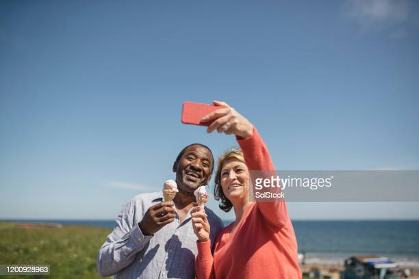 cheerful senior couple holding ice creams taking selfie at seaside - candid stock pictures, royalty-free photos & images
