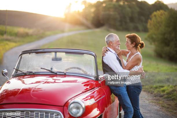 A cheerful senior couple in love standing by cabriolet on a road trip in summer at sunset.