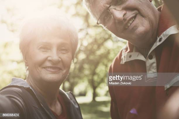 Fröhlich, älteres Paar in Sportbekleidung eine Kamera zusammenzuhalten.