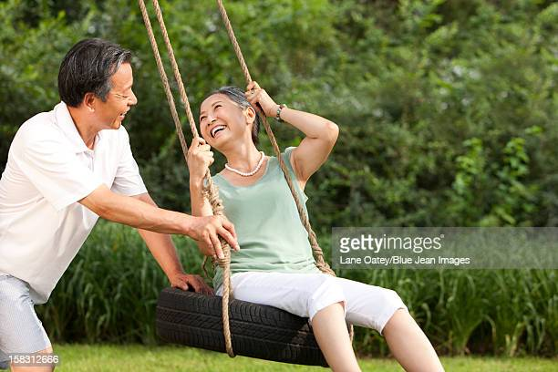 cheerful senior couple playing on a swing - partire bildbanksfoton och bilder