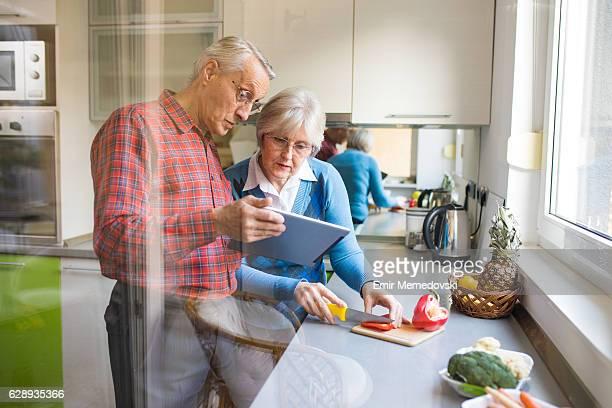 Cheerful senior couple preparing healthy meal using online recipe