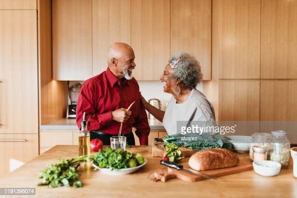 cheerful senior couple preparing vegan meal in kitchen - healthy stock pictures, royalty-free photos & images