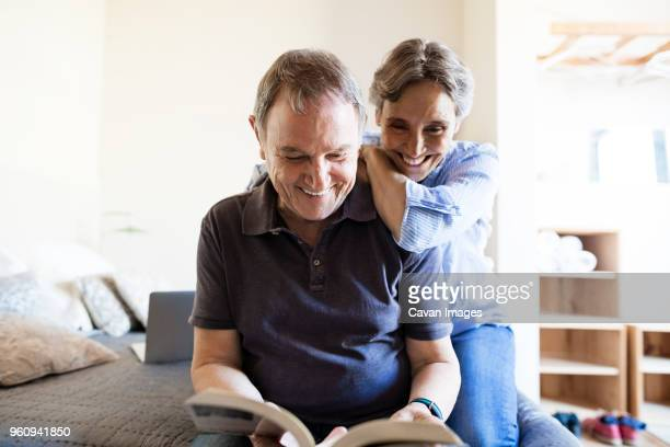 Cheerful senior couple reading book in bedroom