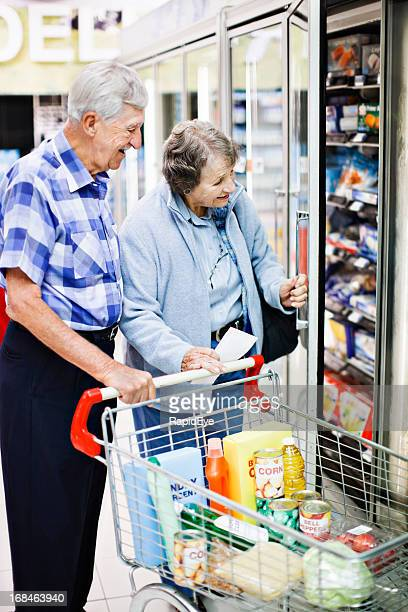 Cheerful senior couple shopping together check supermarket fridge