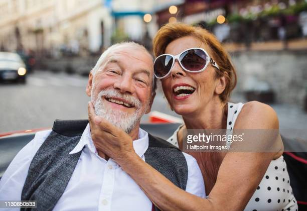 A cheerful senior couple sitting in cabriolet on a road trip in summer in town.