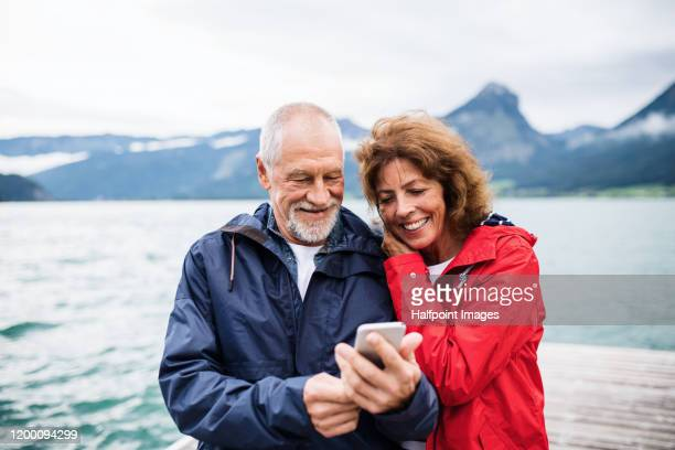 cheerful senior couple tourist standing by lake in nature on holiday, using smartphone. - travel stock pictures, royalty-free photos & images