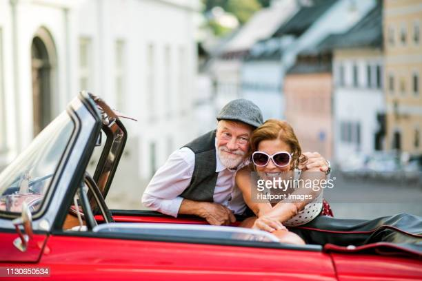A cheerful senior couple with cabriolet on a road trip in summer in town.
