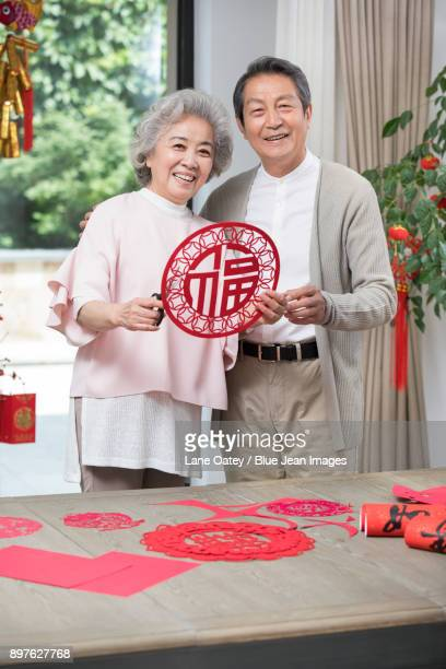 Cheerful senior couple with Chinese New Year paper-cut