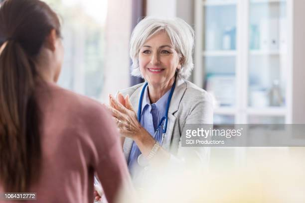 cheerful senior doctor talks with patient - gynecologist stock pictures, royalty-free photos & images