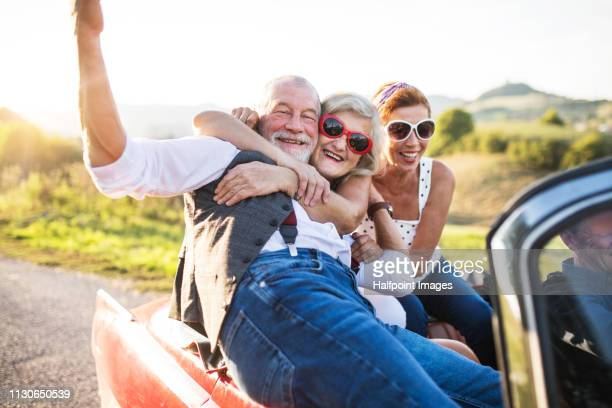 Cheerful senior friends in cabriolet on a road trip in summer at sunset, having fun.