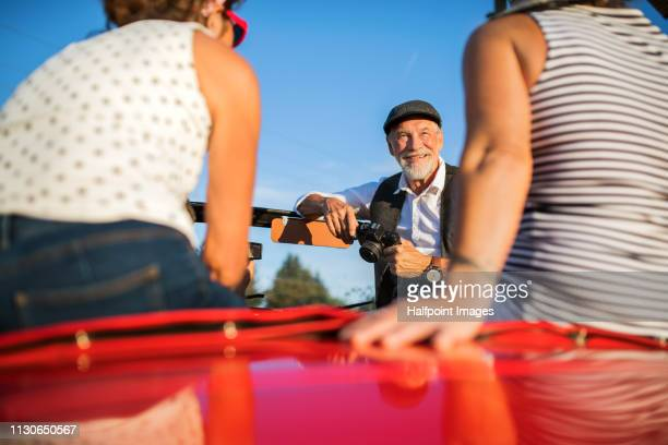 Cheerful senior friends in cabriolet with a camera on a road trip in summer, having fun.