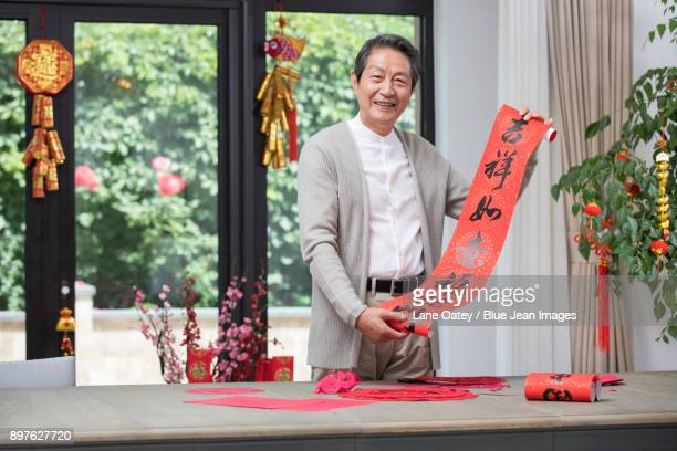 Cheerful senior man celebrating Chinese New Year with couplet