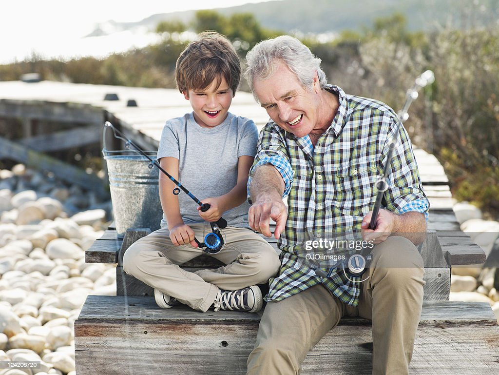 Cheerful senior man fishing with boy on pier : Stock Photo