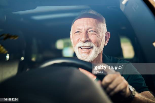cheerful senior man having fun in his new car. - cheerful stock pictures, royalty-free photos & images