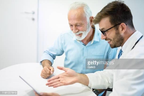 vrolijke senior man op zoek naar grote medische examen resultaten met arts. - goed nieuws stockfoto's en -beelden