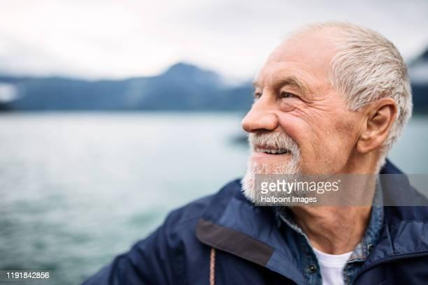 cheerful senior man tourist standing by lake in nature on holiday. - senioren mannen stockfoto's en -beelden