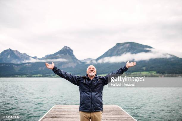 cheerful senior man tourist standing by lake in nature on holiday, stretching arms. - manteau et veste photos et images de collection