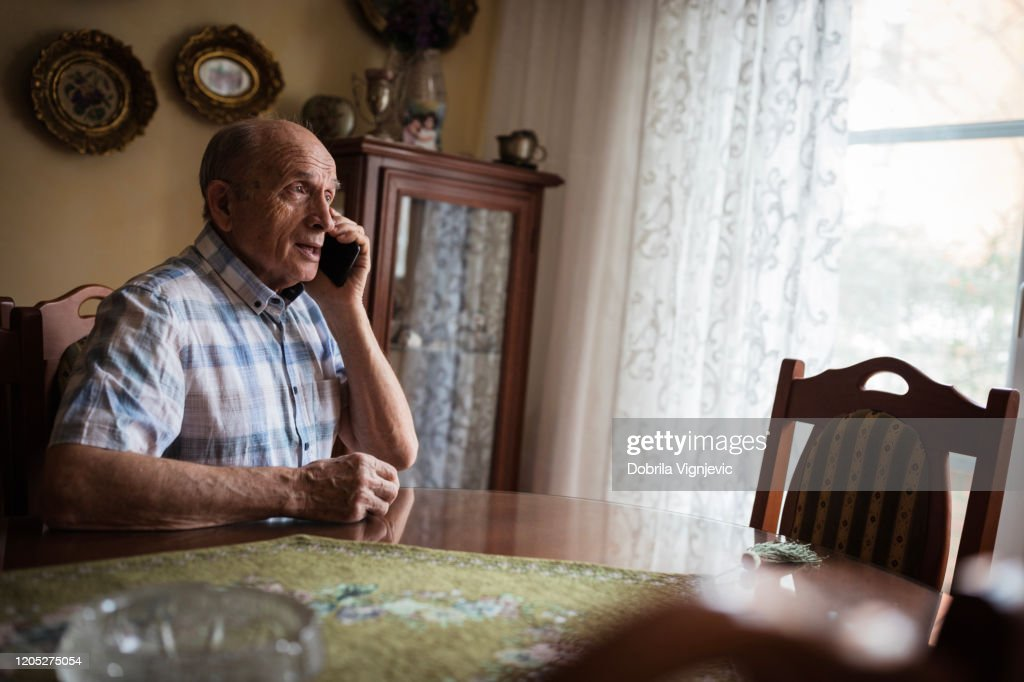 Cheerful senior man using mobile phone at home : Stock Photo