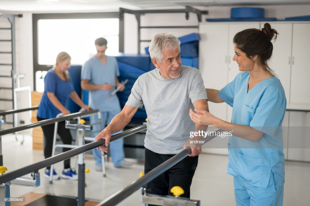 Cheerful senior man using parallel bars to walk and physiotherapist smiling at him happy : Stock Photo