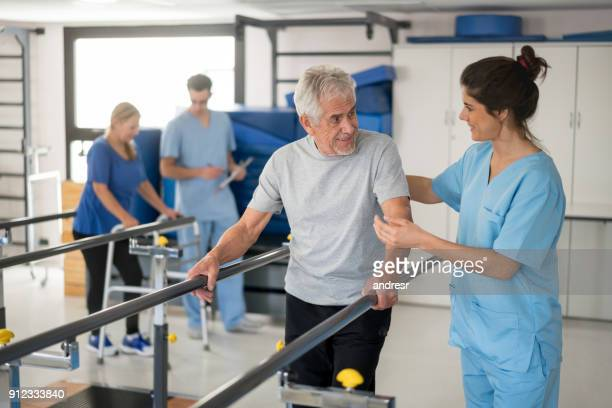 Cheerful senior man using parallel bars to walk and physiotherapist smiling at him happy