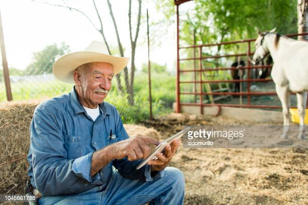 cheerful senior mexican man sitting on haystack with digital tablet - medium shot stock pictures, royalty-free photos & images