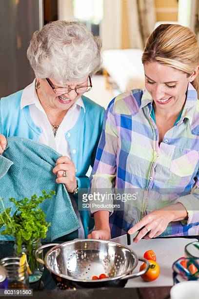 Cheerful senior mother and her mid adult daughter prepare dinner