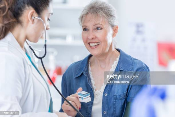 Cheerful senior patient talks with female doctor