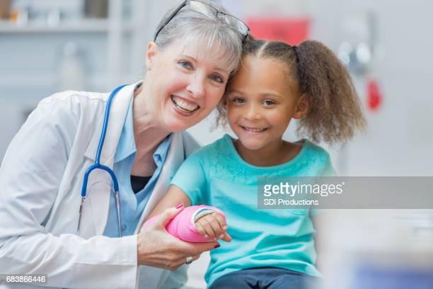 Fröhliche leitender Kinderarzt mit Patienten