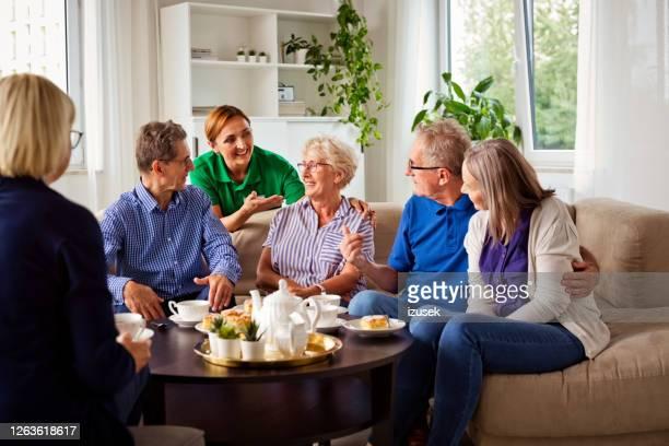 vrolijke hogere mensen in pensioneringshuis - izusek stockfoto's en -beelden