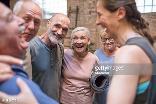 Cheerful senior people with instructor in gym