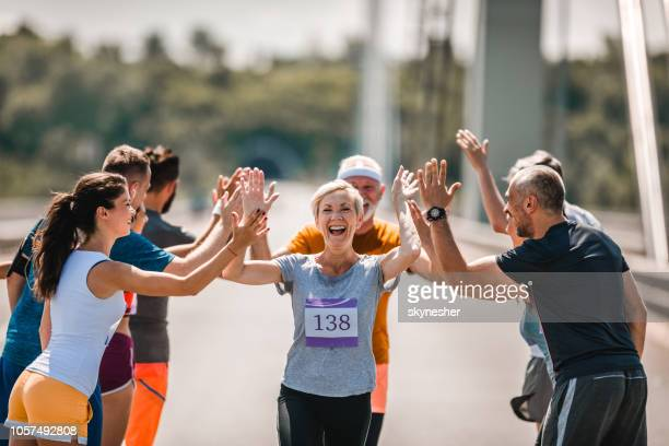 Cheerful senior runner greeting her supporters during marathon race.