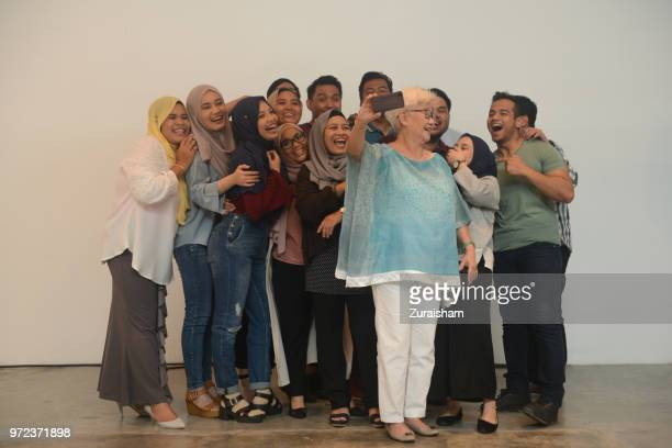 a cheerful senior woman and young friends having gathering in a studio, taking selfie photos with a mobile phone - malaysische kultur stock-fotos und bilder