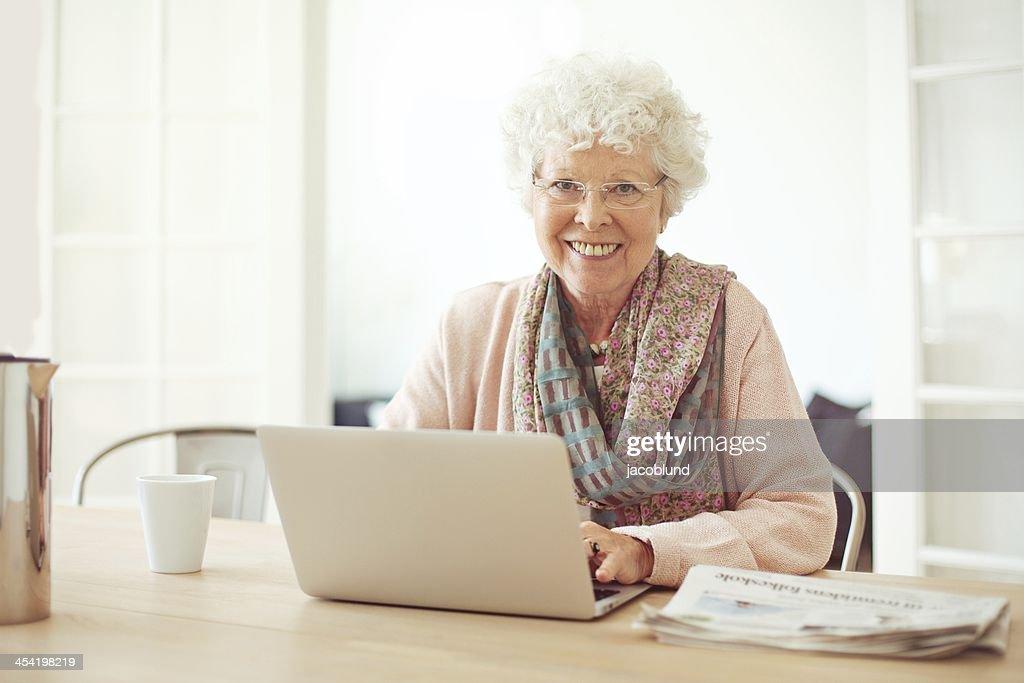 Alegre mujer Senior en casa con ordenador portátil : Foto de stock