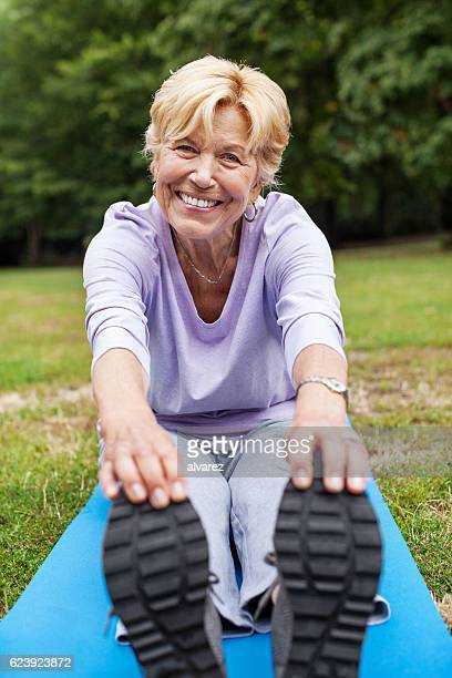 Cheerful senior woman doing yoga workout in park