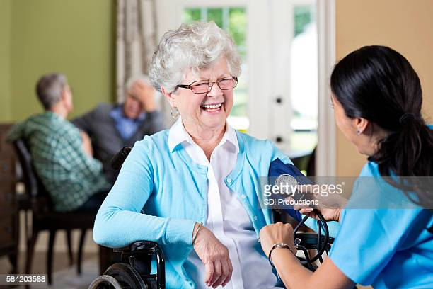 Cheerful senior woman getting her blood pressure taken