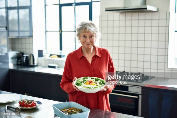 cheerful senior woman holding fresh salad in modern kitchen - seniore vrouwen stockfoto's en -beelden