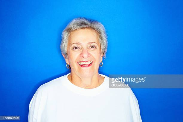 Cheerful senior woman laughing against blue background