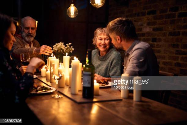 Cheerful senior woman listening to son in law and smiling