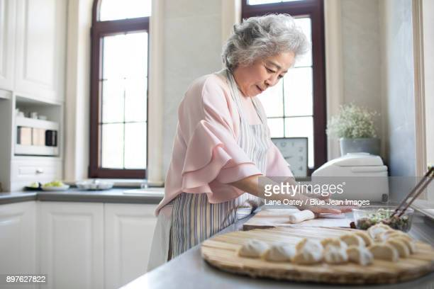 Cheerful senior woman making dumplings in kitchen